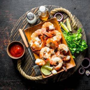 Fried shrimps on tray with herbs, sauce and spices.