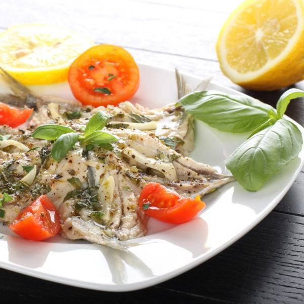 Salad marinated sardines with basil and tomato on complex background