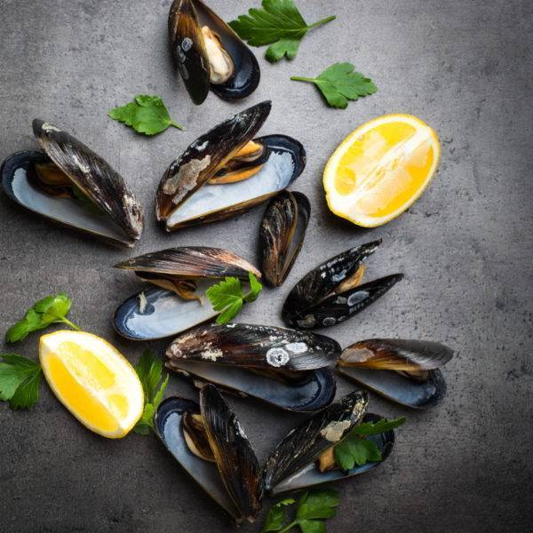 Boiled mussels on black stone table.
